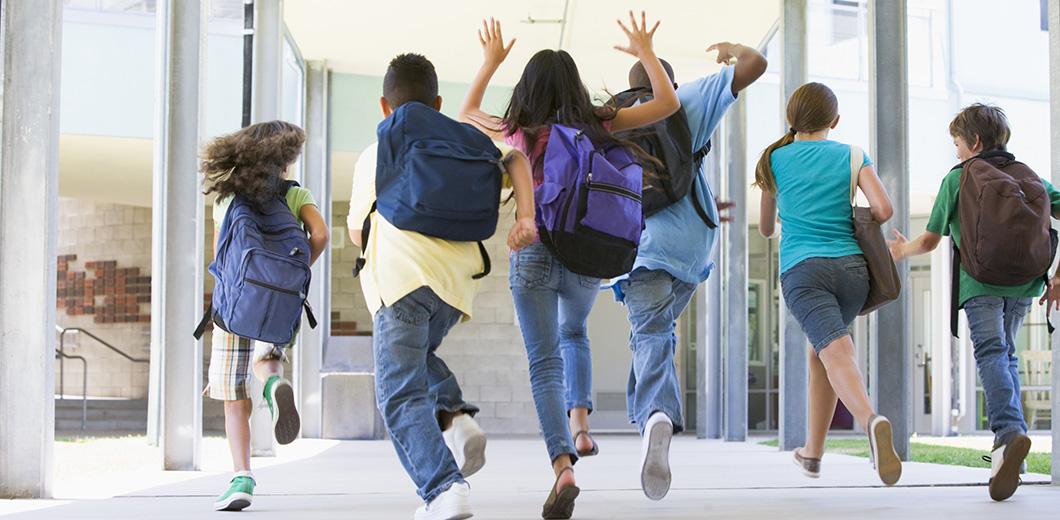 Kinder rennen über einen Schulflur