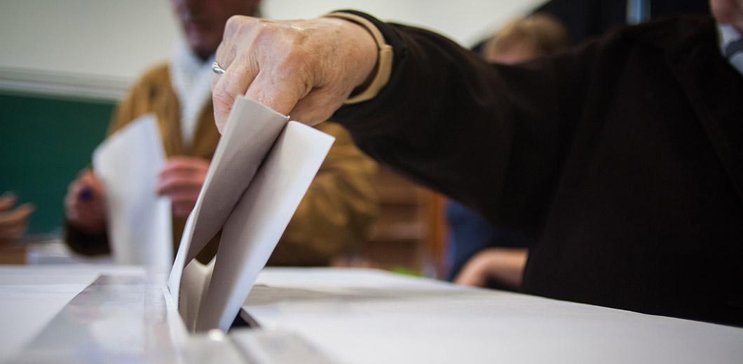 Wahlunterlagen werden in eine Wahlurne eingeworfen