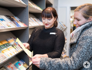 A staff member of the tourist information helps with the selection of brochures
