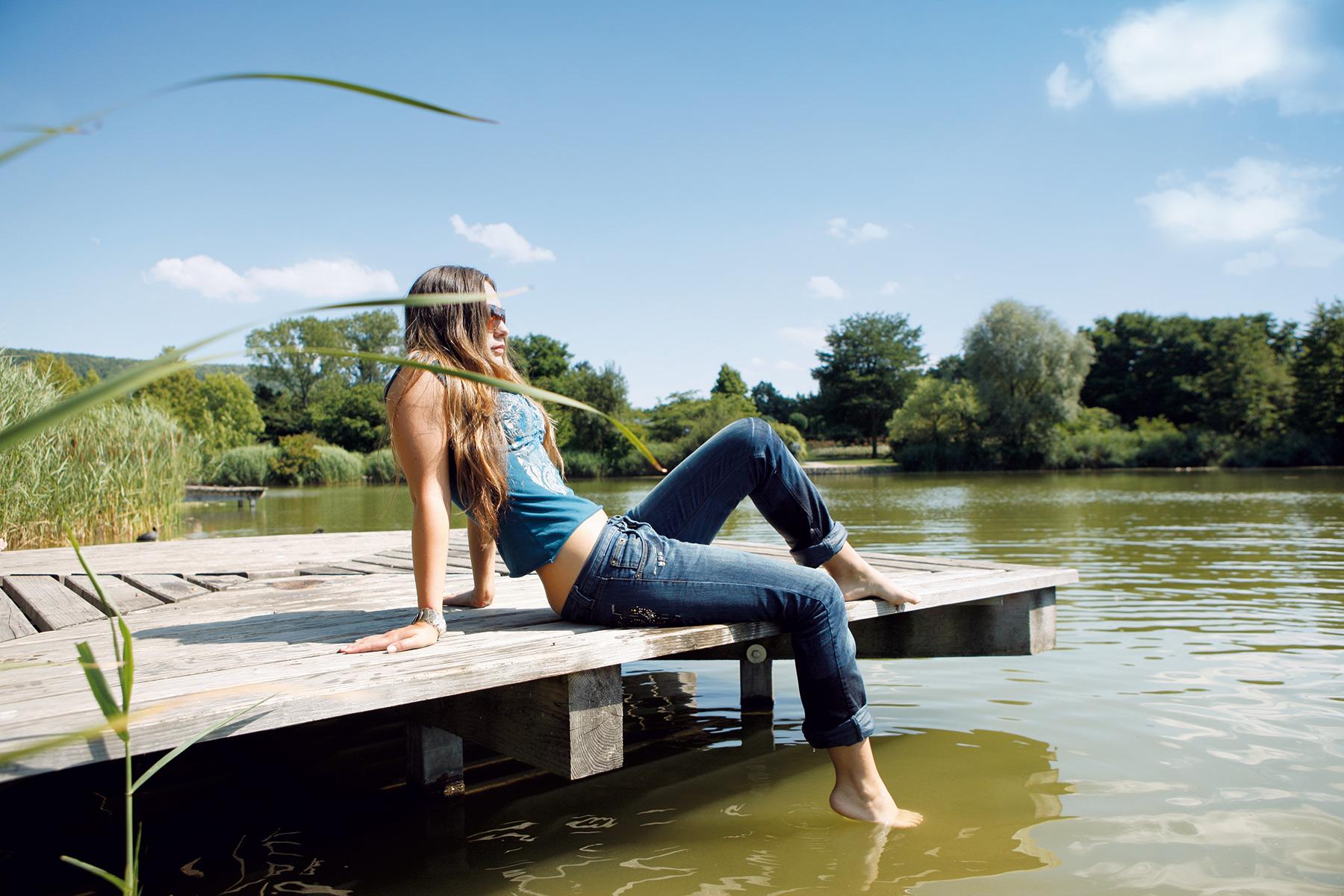 Junge Frau sitzt auf einem Steg am Grüttsee