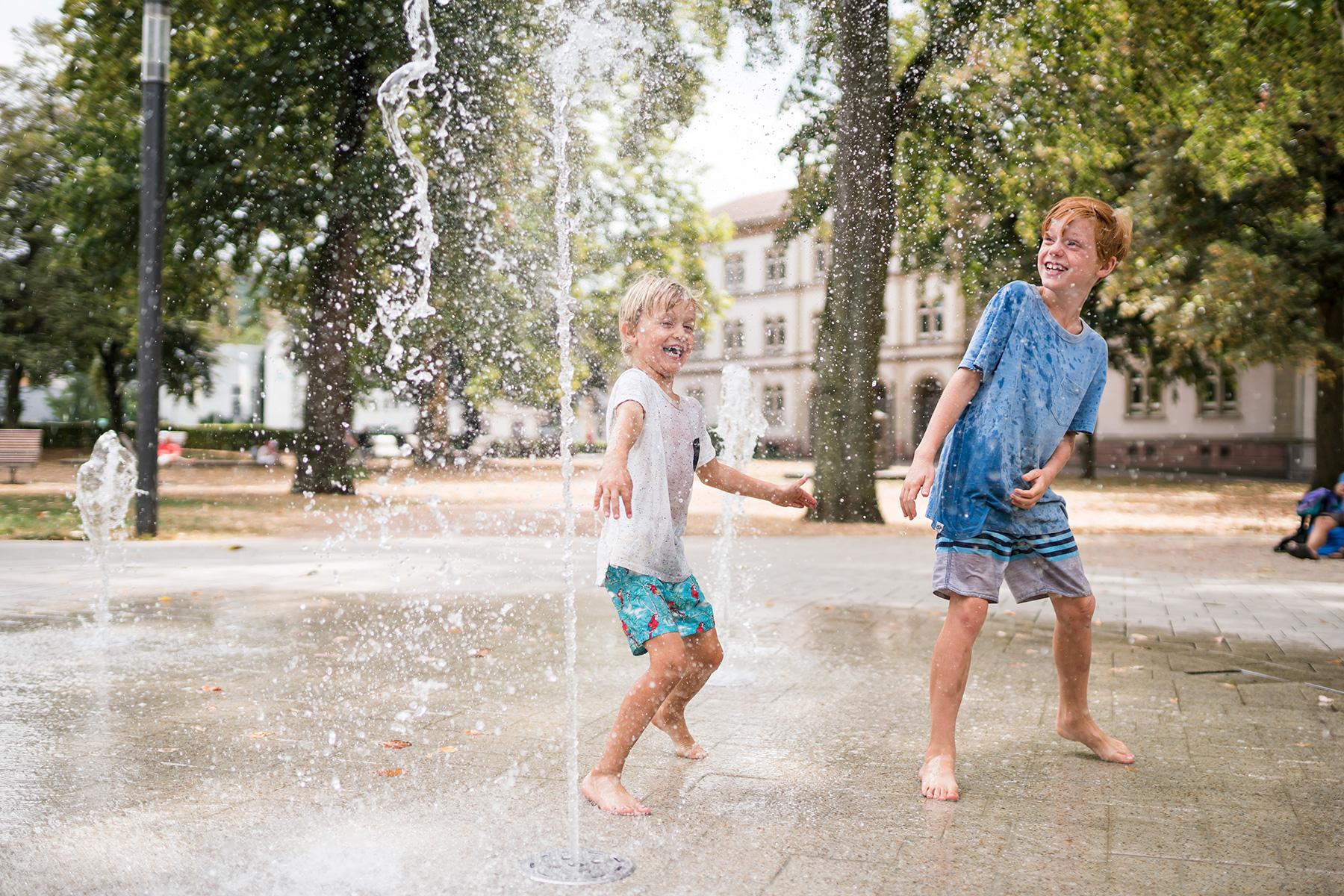 Kinder erfrischen sich an den Wasserspielen beim Hebelpark