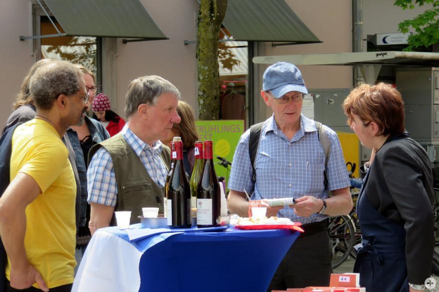 Besucherinnen und Besucher des Lörracher Frühlingsfestes beim Gespräch an einem Stehtisch