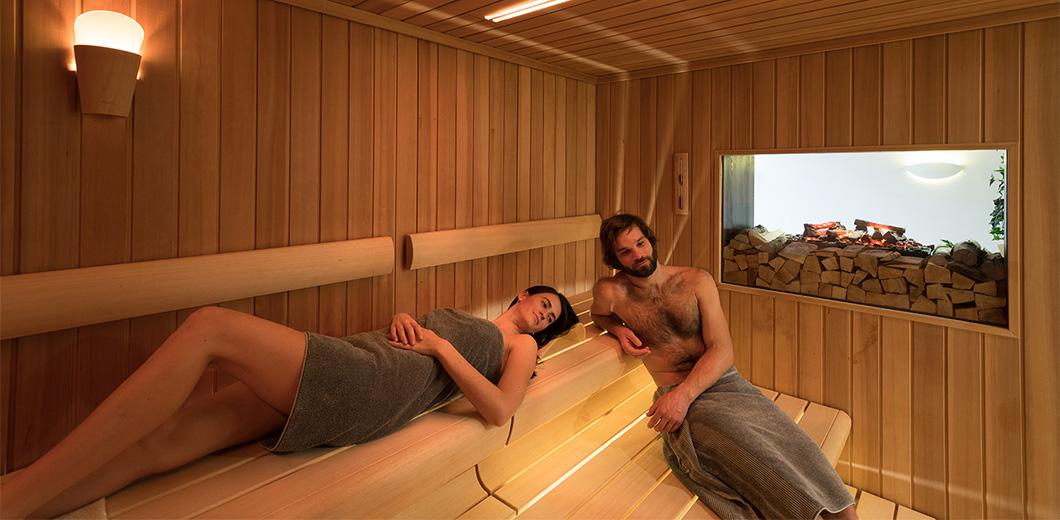 Eine Frau und ein Mann liegen auf der Saunabank